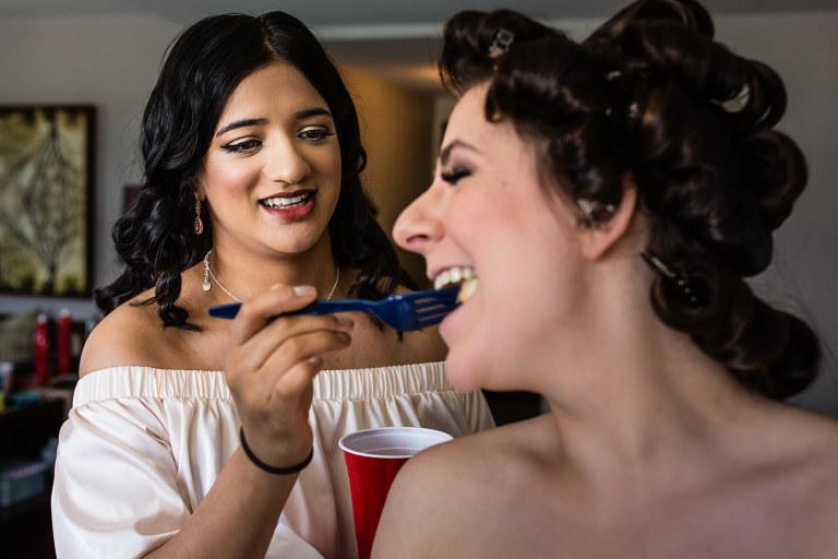 Helpful bridesmaid feeding the bride