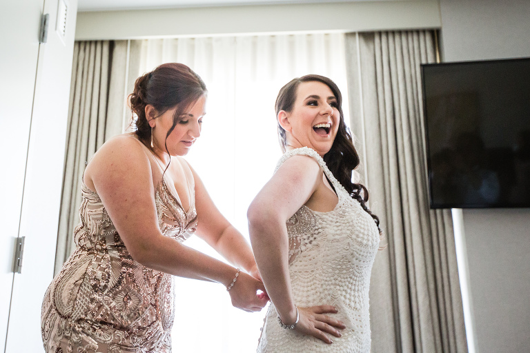 bridemaid zipping up wedding gown in Jersey City